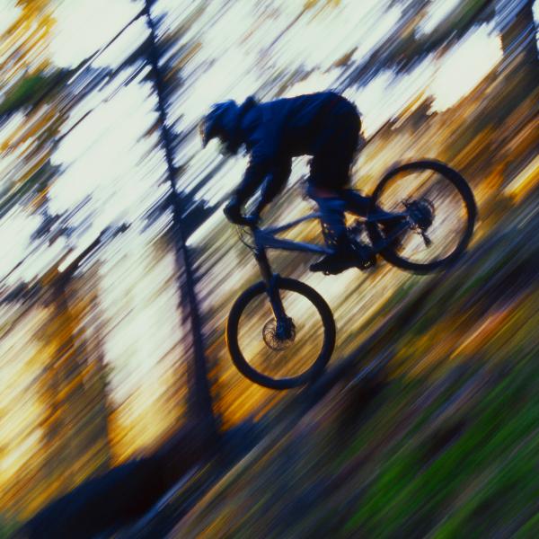 Henkilö ajaa pyörällä rinnettä alas.