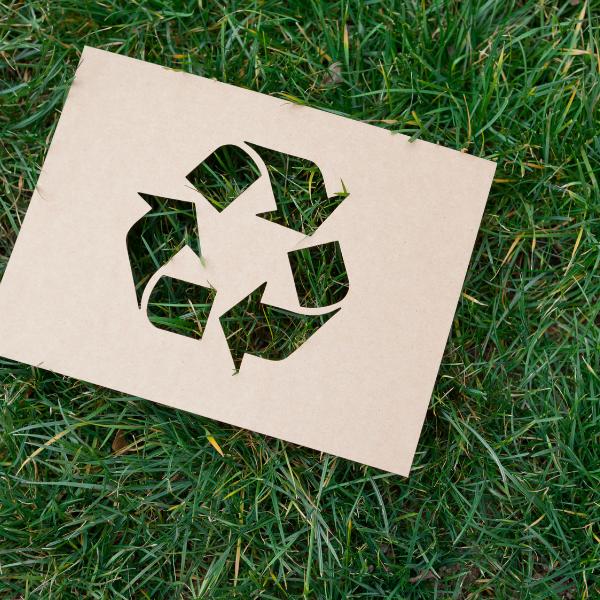 Kierrätystä kuvaava symboli nurmikolla.